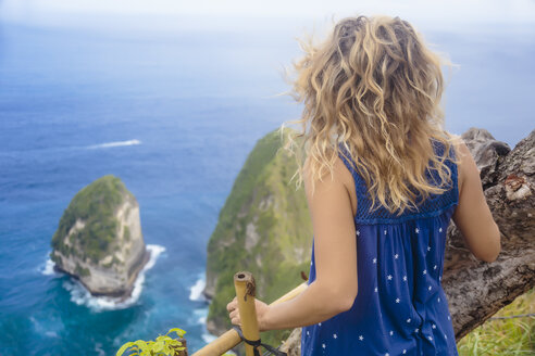Rear view of adult woman admiring ocean coastline from cliff of Nusa Penida island, Bali, Indonesia - AURF07525