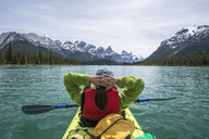 Woman kayaking on Maligne Lake with Canadian Rockies in background, Jasper National Park, Alberta, Canada - AURF07576