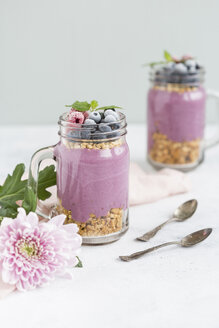 Two glasses of yoghurt with peanut granola, aronia powder and topping of chopped hazelnuts and frozen berries - JUNF01302