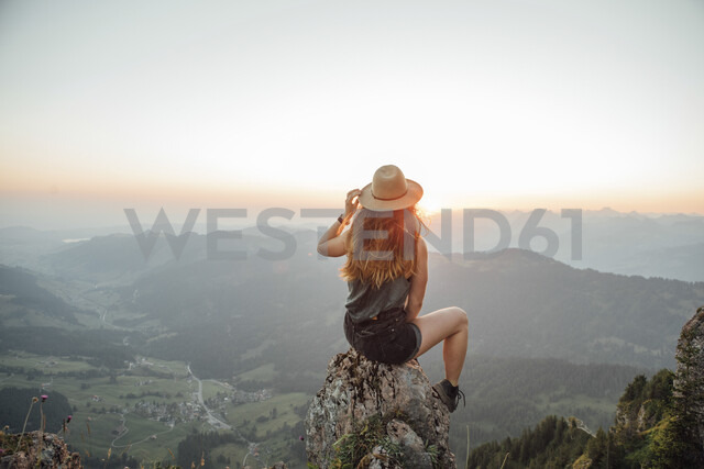 Switzerland, Grosser Mythen, young woman on a hiking trip sitting on a rock at sunrise - LHPF00040 - letizia haessig photography/Westend61