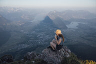 Switzerland, Grosser Mythen, young woman on a hiking trip sitting on a rock at sunrise drinking from cup - LHPF00043