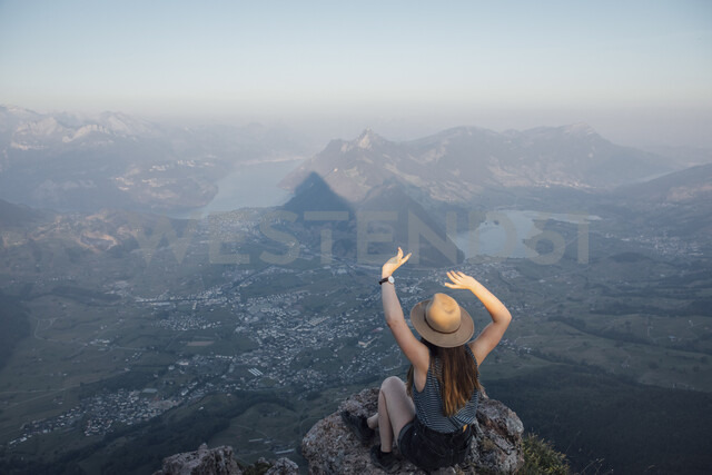 Switzerland, Grosser Mythen, young woman on a hiking trip sitting on a rock at sunrise - LHPF00046 - letizia haessig photography/Westend61