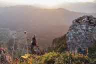Switzerland, Grosser Mythen, young woman on a hiking trip sitting on a rock at sunrise - LHPF00049