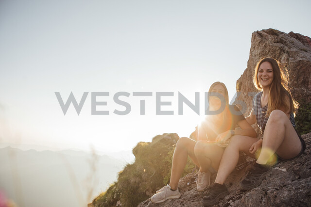 Switzerland, Grosser Mythen, two happy girlfriends on a hiking trip having a break at sunrise - LHPF00055