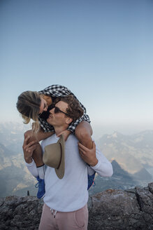 Switzerland, Grosser Mythen, young man kissing girlfriend on his shoulders - LHPF00067