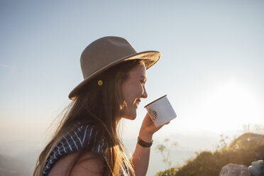 Happy young woman on a hiking trip at sunrise holding a cup - LHPF00073