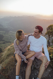 Switzerland, Grosser Mythen, happy young couple on a hiking trip having a break at sunrise - LHPF00082