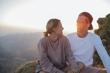 Switzerland, Grosser Mythen, happy young couple on a hiking trip having a break at sunrise - LHPF00085