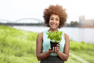 Portrait of smiling woman holding plant outdoors - FMKF05249