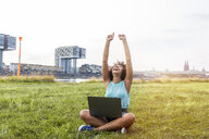 Germany, Cologne, cheering woman sitting on a meadow using laptop - FMKF05255
