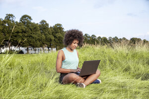 Woman sitting on meadow using laptop - FMKF05258