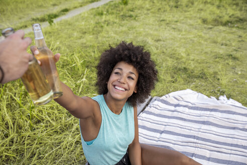 Happy woman sitting outdoors clinking beer bottle - FMKF05261