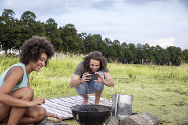 Smiling young man with girlfriend taking a picture of barbecue grill in the nature - FMKF05264