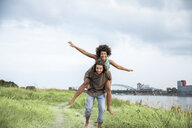 Germany, Cologne, happy carefree couple at the riverside - FMKF05267