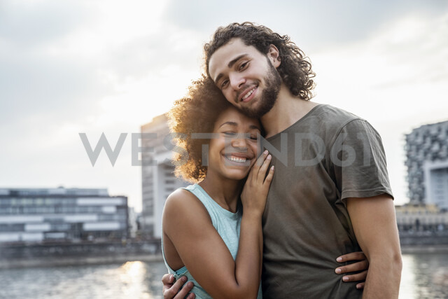 Germany, Cologne, portrait of happy couple at the riverside - FMKF05270
