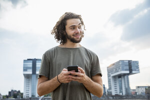 Germany, Cologne, smiling young man holding cell phone looking sideways - FMKF05273
