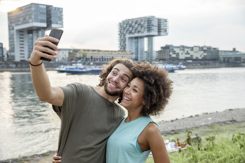 Germany, Cologne, happy couple taking a selfie at the riverside - FMKF05276