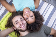 Portrait of happy couple lying on a blanket outdoors - FMKF05285