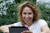 Portrait of smiling woman with digital tablet - HHLMF00495