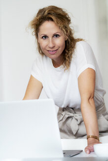 Portrait of smiling woman with laptop - HHLMF00507