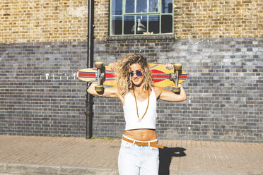 Portrait of smiling young woman carrying skateboard in the city - WPEF00795