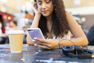 Young woman sitting at a table looking at cell phone - WPEF00798
