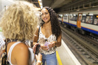 UK, London, two young women with cell phones waiting at underground station platform - WPEF00801