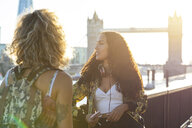 UK, London, two friends together in the city with Tower Bridge in background at sunset - WPEF00807