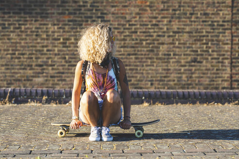 Young woman sitting on a skateboard with brick wall in background - WPEF00810