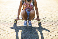 Close-up of young woman sitting on a skateboard in sunlight - WPEF00813