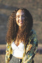 Portrait of smiling young woman with curly hair outdoors - WPEF00819