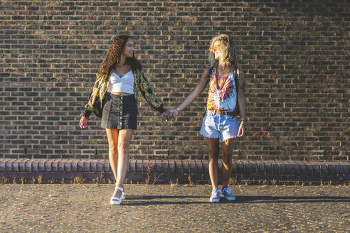 Two young women holding hands in front of brick wall - WPEF00822
