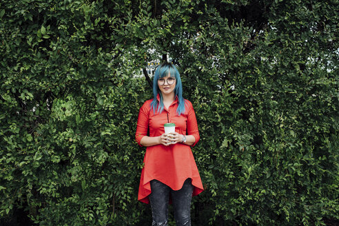 Portrait of young woman with dyed blue hair standing in front of a hedge with beverage - VPIF00833