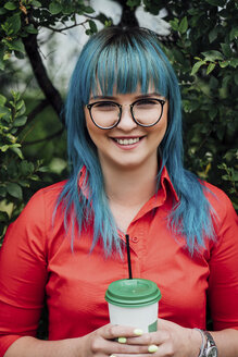 Portrait of smiling young woman with dyed blue hair and beverage - VPIF00836