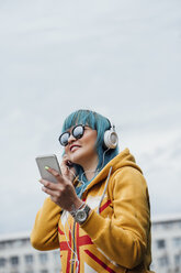 Portrait of young woman with dyed blue hair listening music with smartphone and headphones - VPIF00839