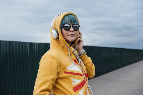 Portrait of young woman with dyed blue hair listening music with  headphones - VPIF00845