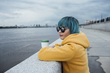 Young woman with dyed blue hair leaning on a wall looking at distance - VPIF00848