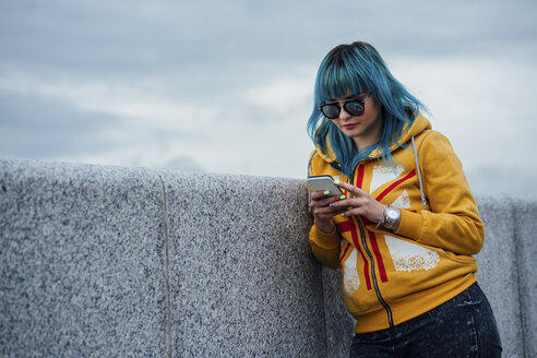 Portrait of young woman with dyed blue hair leaning against wall looking at cell phone - VPIF00851