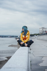 Young woman with dyed blue hair sitting on a wall looking at distance - VPIF00854
