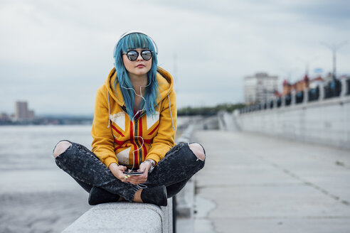 Young woman with dyed blue hair sitting on a wall listening music with headphones and smartphone - VPIF00857