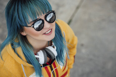 Portrait of young woman with dyed blue hair and headphones looking up - VPIF00863