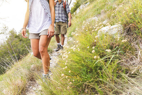 Italy, Massa, legs of young couple hiking in the Alpi Apuane mountains - WPEF00835