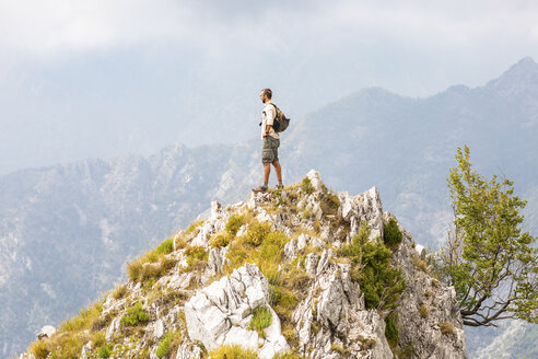 Italy, Massa, man standing on top of a peak in the Alpi Apuane mountains - WPEF00853