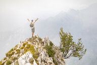 Italy, Massa, man cheering on top of a peak in the Alpi Apuane mountains - WPEF00856