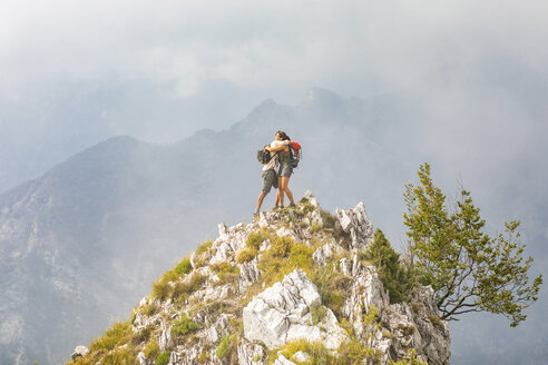Italy, Massa, happy couple hugging on top of a peak in the Alpi Apuane mountains - WPEF00862