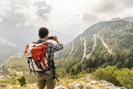 Italy, Massa, man hiking and taking a picture of the view in the Alpi Apuane - WPEF00871