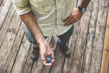Close-up of man standing on boardwalk holding a compass - WPEF00889