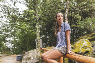 Italy, Massa, smiling young woman sitting on a wooden fence in the Alpi Apuane - WPEF00910