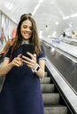 UK, London, portrait of smiling businesswoman standing on escalator looking at cell phone - MGOF03786