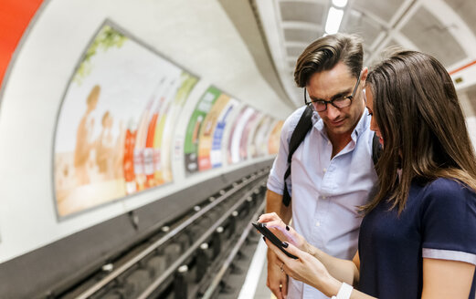 UK, London, young couple standing at underground station platform looking at cell phone - MGOF03789